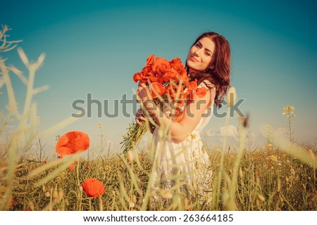 Young beautiful girl in the field with a poppies bouquet. Free Happy Woman Enjoying Nature. Beauty Girl Outdoor. Freedom concept. Beauty Girl over Sky and Sun.Enjoyment. - stock photo