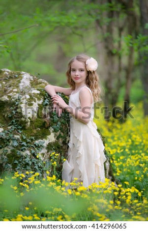 young beautiful girl in the forest near a large stone on a background of yellow flowers