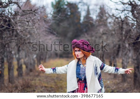 Young beautiful girl in the garden in late autumn dressed in exotic bright clothes in the style of ethnic and boho with a turban on his head, and patterns on the face