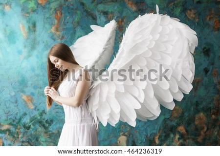 young beautiful girl in the image of an angel with white wings