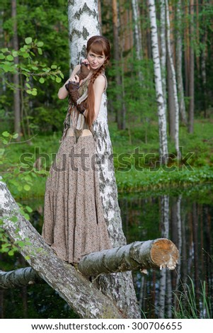 Young beautiful girl in the summer forest