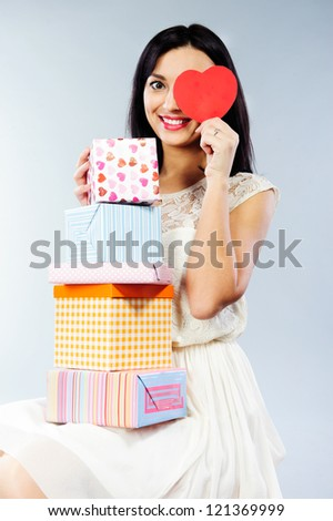 Young beautiful girl in white dress holding stack of present boxes and red paper Valentine heart - stock photo