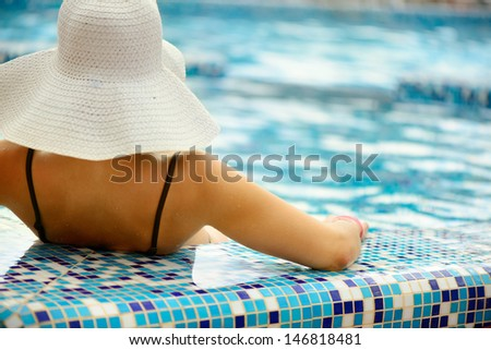 Young beautiful girl in white hat relaxing at swimming pool. Rear view - stock photo