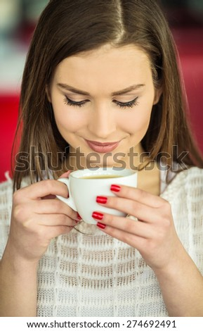 Young beautiful girl in  white pullover sitting in urban cafe with a cup of coffee. - stock photo