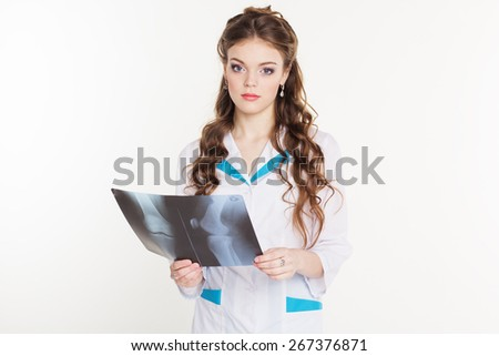 Young beautiful girl intern looking at the x-ray picture of knee in hospital - stock photo