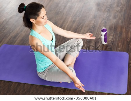 young beautiful girl is engaged in yoga in a studio.Yoga at home. meditation, yoga studio in daylight from the window. The girl in the lotus position. Purple yoga mat and water bottle. - stock photo