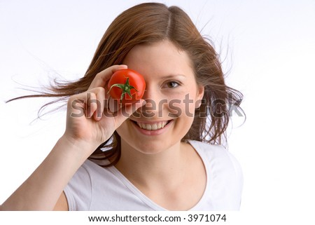 young, beautiful girl is holding a tomato to her eye - stock photo