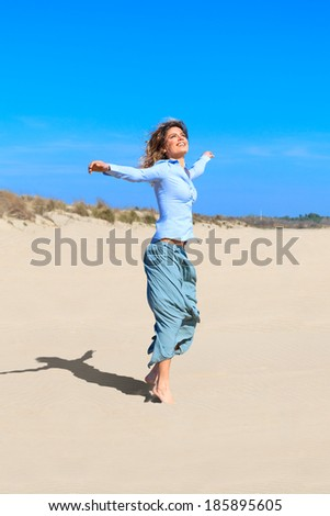 young beautiful girl is jumping up in the air at the beach