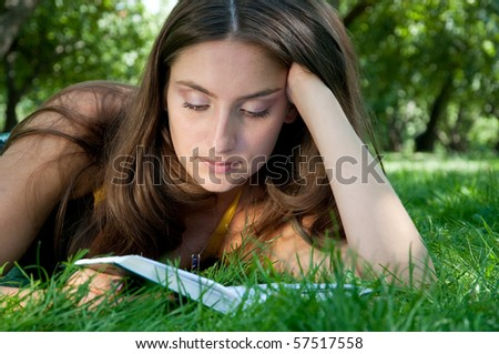 Young beautiful girl is reading book in the summer park