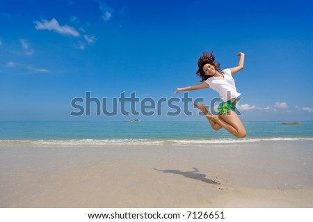 young beautiful girl jumping gracefully at the beach feeling free and happy