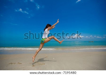 young beautiful girl jumping happily at the beach