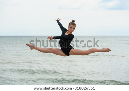 Young beautiful girl jumps outdoors over sea background - stock photo