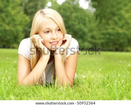 Young beautiful girl laying on the grass