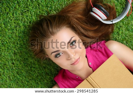 Young beautiful girl laying on the grass in park holding a book. Summertime, leisure and education concept Top view - stock photo
