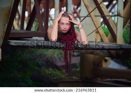 Young beautiful girl lies on a scaffold at a construction site