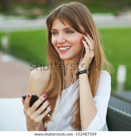Young beautiful girl listening to MP3 player on the street in a cafe. - stock photo