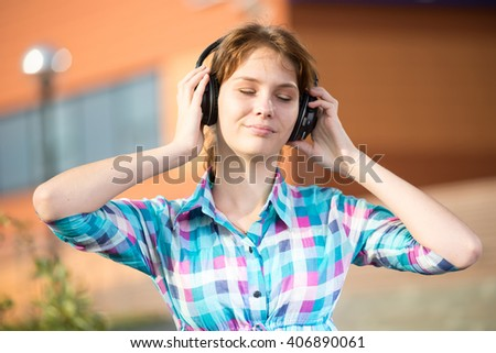 Young beautiful girl listening to music player on the street. tudent woman at campus park.