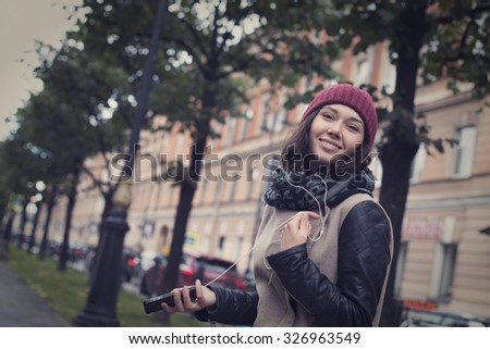 Young beautiful girl listening to music with headphones on white smartphone and dancing in the center of St. Petersburg - stock photo