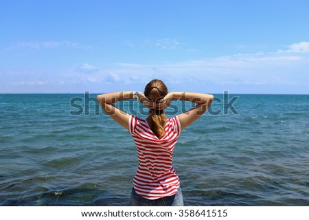 Young beautiful girl looks at the blue sea at summertime - stock photo