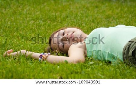 Young beautiful girl lying down on grass - stock photo