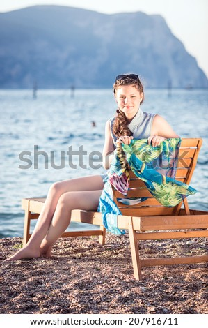 Young beautiful girl lying on a chaise lounge on the beach