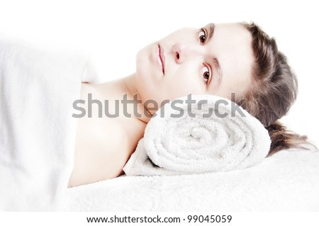 Young beautiful girl lying on a massage table at spa - stock photo
