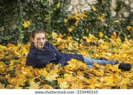 Young beautiful girl lying on the leaves in the autumn park. - stock photo