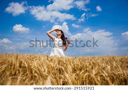 Young beautiful girl on a field of wheat looking upwards and celebrate life