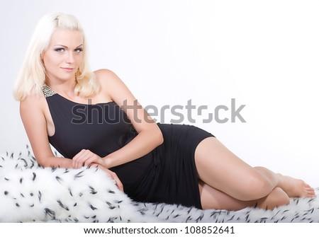 Young beautiful girl on white fur - stock photo
