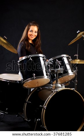 Young beautiful girl playing drums against a black.