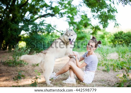 Young beautiful girl playing with a dog. Playing with the dog on the field. Close-up portrait. Siberian husky. - stock photo