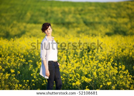 Young beautiful girl posing on a yellow field.