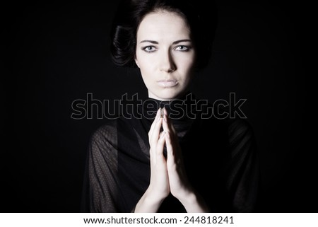 young beautiful girl praying. on a black background - stock photo