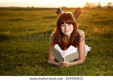 Young beautiful girl reading a book in park - stock photo