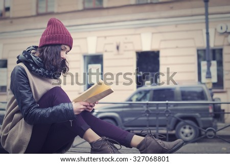 Young beautiful girl reading a book or tutorial in a park in the center of St. Petersburg - stock photo