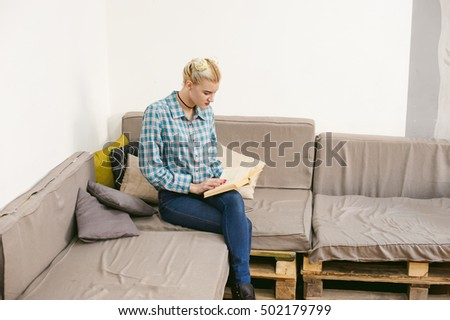 young beautiful girl reading a book sitting on a sofa in the room