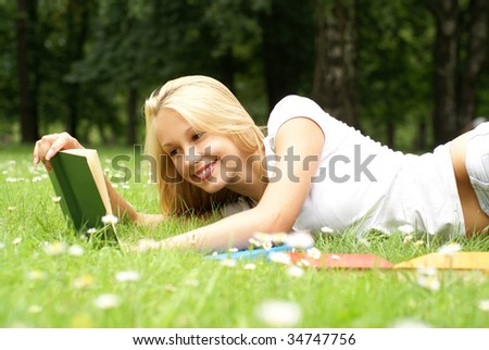 Young beautiful girl reading in the park