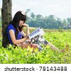 young beautiful girl reading on the grass - stock photo