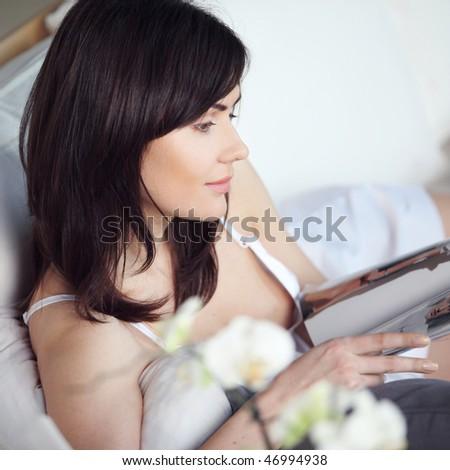 young beautiful girl reads magazine - stock photo