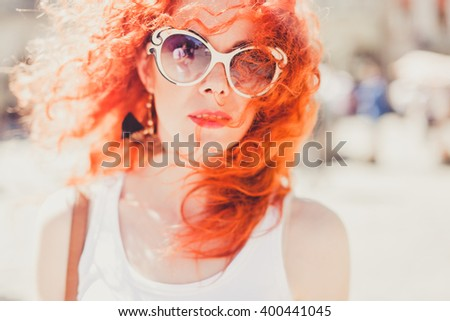 young beautiful girl red hair sunglasses, cute, holding, poses outside in the sun, pretty woman outdoor portrait, close up - stock photo
