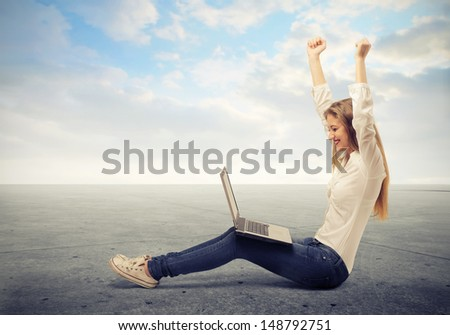 young beautiful girl rejoices looking at the computer - stock photo