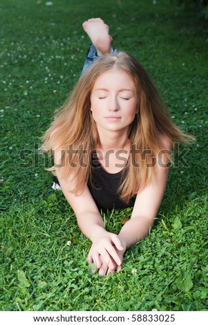 Young beautiful girl relaxing on the field (Selective focus) - stock photo