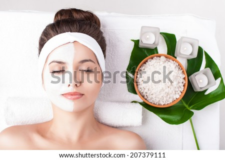 Young beautiful girl relaxing with facial masks on over white background - stock photo