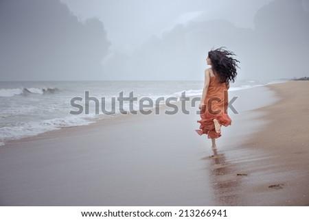 Young beautiful girl running in beach. - stock photo