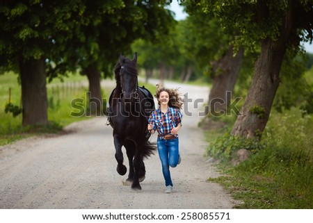 Young beautiful girl runs with the horse at summer time - stock photo