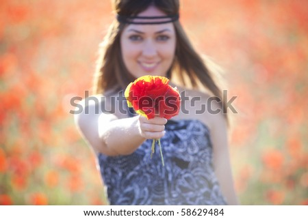 Young beautiful girl showing a poppies bouquet. - stock photo