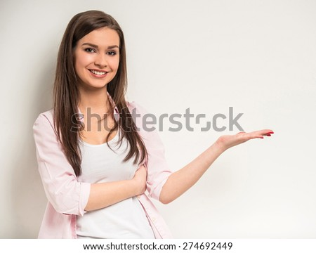 Young beautiful girl showing copy space over grey background. - stock photo