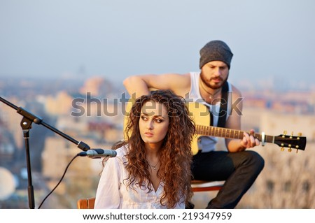 Young beautiful girl singing with a guitar player outdoors - stock photo