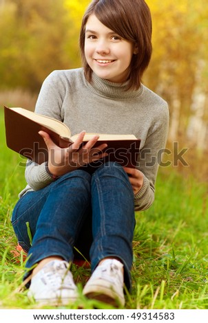 Young beautiful girl sits on bridge and reads interesting book.