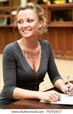 Young beautiful girl sitting at the table, fills out a form and smiling